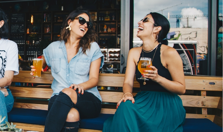 Two women holding drinks laugh sitting outside a restaurant
